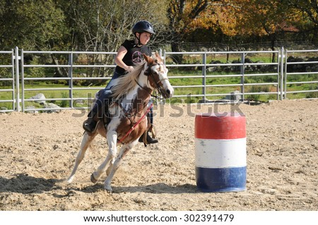 Young girl galloping around a barrel during a barrel race - stock photo