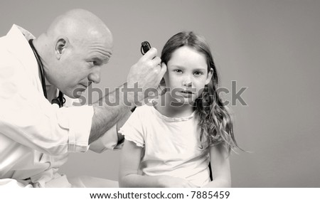 Young Girl Getting Ear Examined by Physician - stock photo