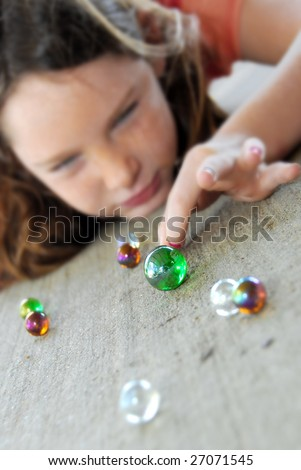 young girl getting ready to flick shooter during marbles - stock photo