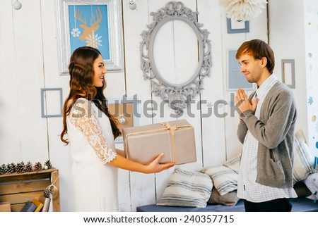 young girl gives a guy a gift - stock photo