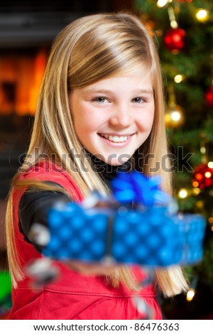 young girl giving a present christmas tree in background - stock photo