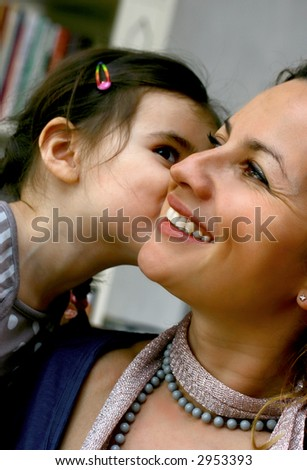 Young girl giving her mother a loving kiss. - stock photo
