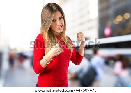 Young girl giving punch on unfocused background