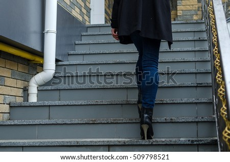 Young girl going up the stairs on the street steps