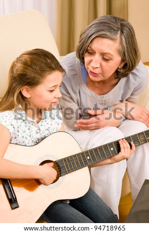 Young girl granddaughter sing play guitar to grandmother smile - stock photo