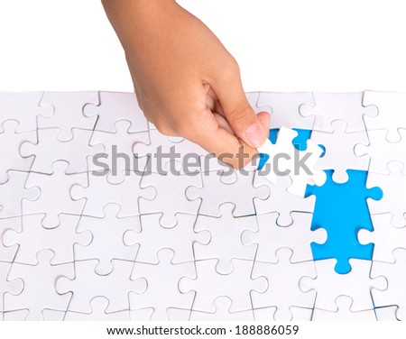 Young girl hand putting jigsaw puzzle pieces together - stock photo