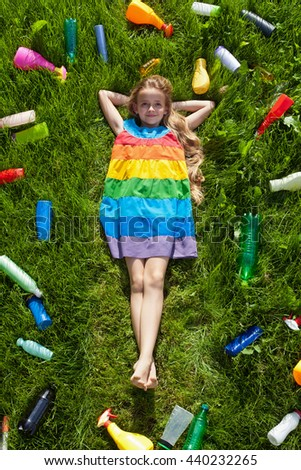 Young girl happy in the grass surrounded by plastic waste - unaware of the danger