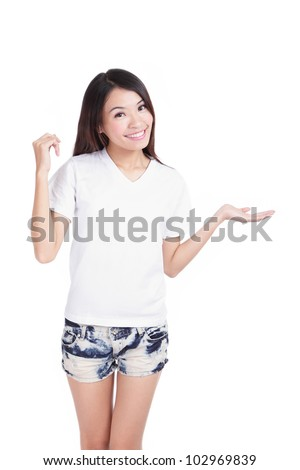 Young Girl happy smile show white T-Shirt with hand introduce something isolated on white background (designer could add any thing on empty copy space), model is a asian woman - stock photo