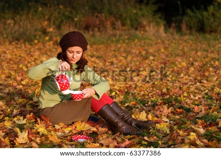 Young girl having a cup of tea in a park with lots of autumn leaves - stock photo