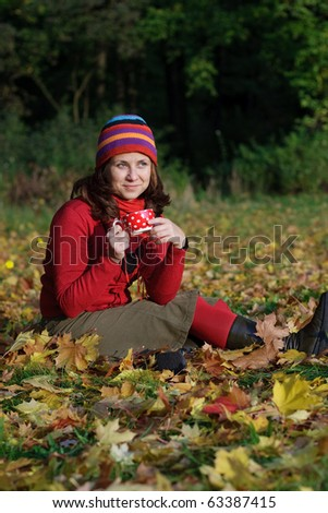 Young girl having a cup of tea in a park with lots of autumn leaves