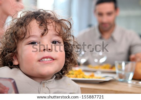Young girl having a meal with her family