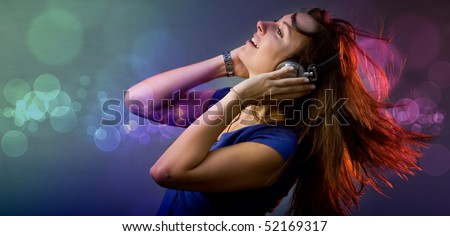Young girl having fun at a disco or nightclub with retro headphones listening to music - stock photo