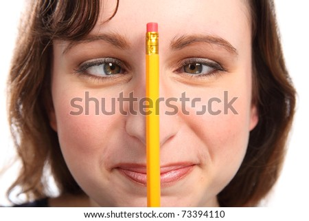 Young girl having fun going cross eyed with a pencil holding on her nose. - stock photo