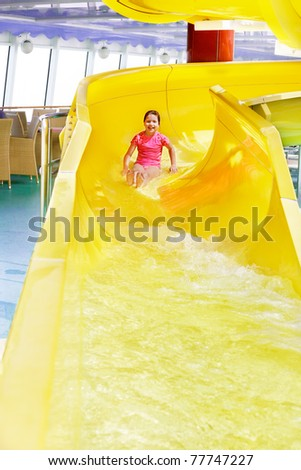 Young girl having fun nearing the end of the water slide - stock photo