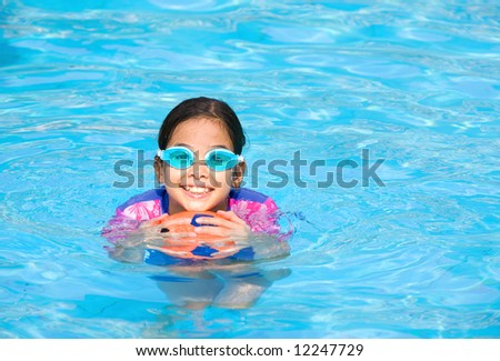 Young girl having fun playing with rubber ball in swimming pool. - stock photo
