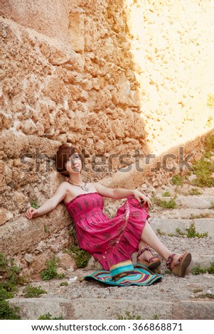 Young girl having rest in the shade of the old town wall - stock photo