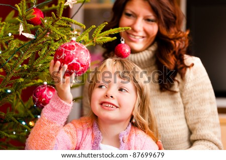 Young girl helping her mother decorating the Christmas tree, holding some Christmas baubles in her hand - stock photo