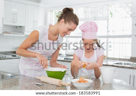 Young girl helping her mother prepare food in the kitchen at home - stock photo