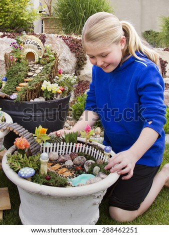 Young girl helping to make fairy garden in a flower pot outdoors