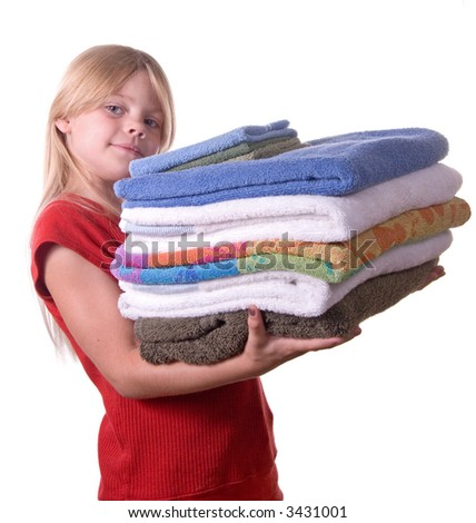 Young girl helping with laundry carrying towels - stock photo
