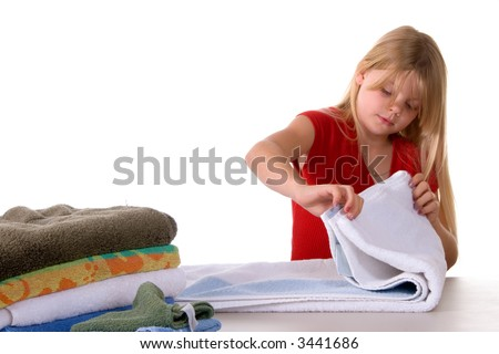 Young girl helping with laundry folding towels - stock photo