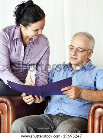 young girl helps a mature man with a form - stock photo