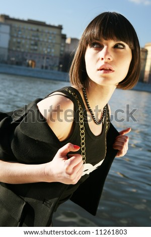 Young girl hiding herself by the river. Moscow city background - stock photo