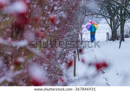 Young girl hold umbrella with colors of rainbow in winter nature - stock photo
