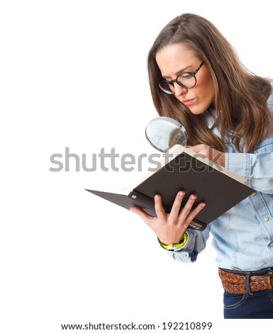 young girl holding a book looking through a magnifying glass - stock photo