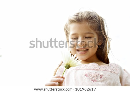 Young girl holding a daisy flower against the sky. - stock photo