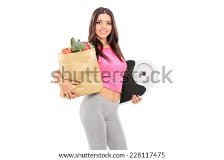 Young girl holding a grocery bag and weight scale isolated on white background - stock photo