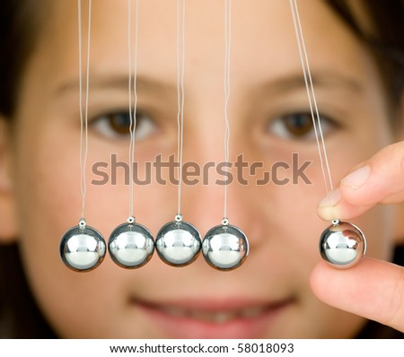 young girl holding a pendulum ball - stock photo