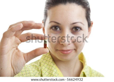 Young girl holding a pill - stock photo