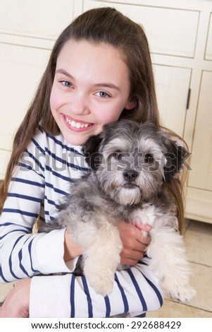 Young girl holding a Puppy. She is looking at the Camera and smiling. - stock photo