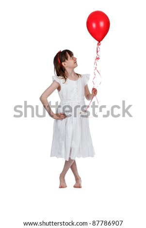 Young girl holding a red balloon on a white background
