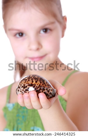 young girl holding a sea shell tiger