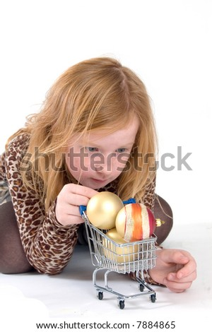 young girl holding a shopping car with christmas balls - stock photo