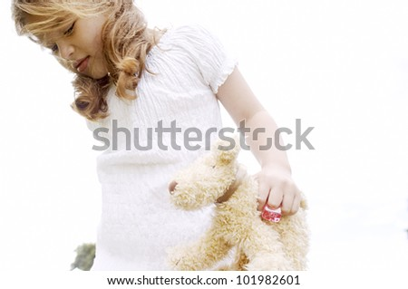 Young girl holding a soft toy against the sky. - stock photo