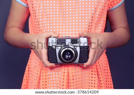 Young girl holding a vintage film camera. Photography, education, fashion and hobby concept.