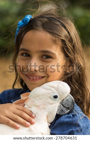 Young girl holding a white parrot - stock photo