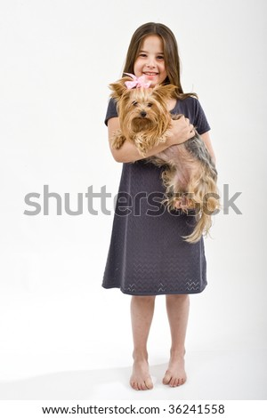 Young girl holding a Yorkshire terrier dog on white - stock photo