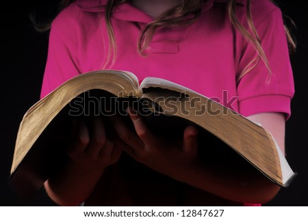Young girl holding Bible in hands - stock photo