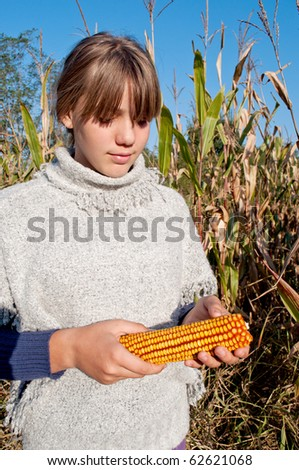 Young girl holding corn - stock photo