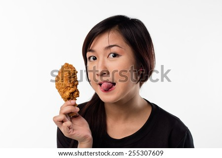 Young girl holding, eating fried chicken - stock photo