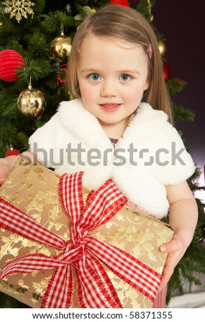 Young Girl Holding Gift In Front Of Christmas Tree - stock photo
