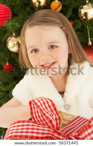Young Girl Holding Gift In Front Of Christmas Tree