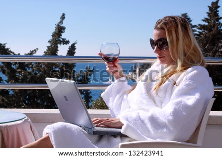 Young girl holding glass with red vine in bathrobe white clothes sitting on balcony with notebook and sea view