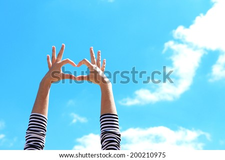 Young girl holding hands in heart shape framing on blue sky background - stock photo