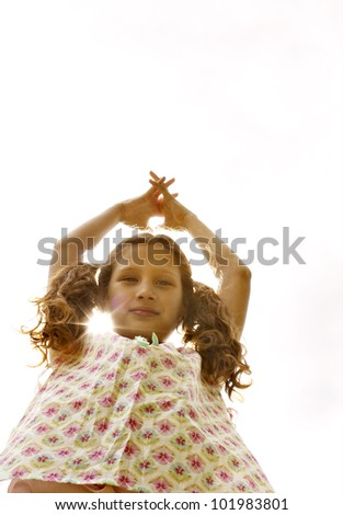 Young girl holding her arms up in the air against the sky with the sun filtering through her neck. - stock photo