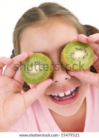 Young girl holding kiwi halves over eyes smiling - stock photo